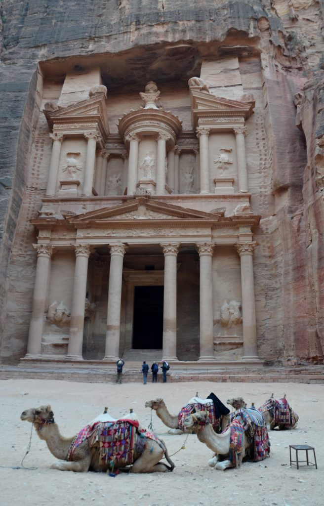 A picture to show the most famous of the whole of visiting Petra, namely the Treasury. The Treasury carved out of the rocks, a grave tomb. In front are a few camels lying down. Some people are standing admiring the building.