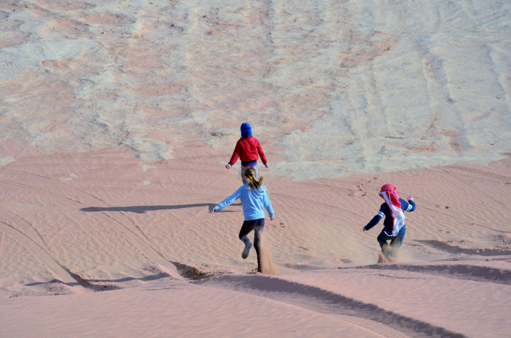 A picture showing that it was fun in the desert. Yuiri and 2 other kids run down a dune in Wadi Rum. The dune is red colored sand. Below is white colored sand.