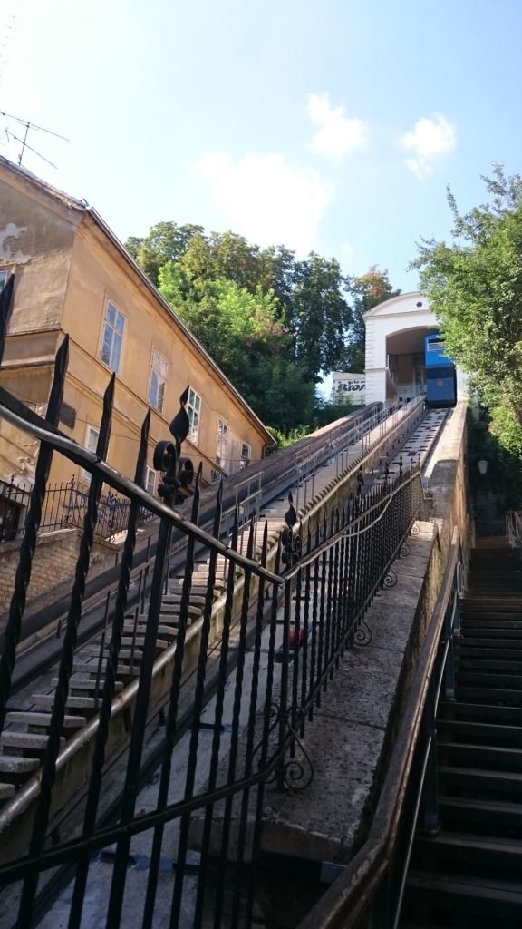 To show the cable track comnnecting the upper and downton parts. You see a steep track, in the tunnel is just visible the back of a blue train cart. Surrounded by green trees and a building on the left. Afternoon in Zagreb.