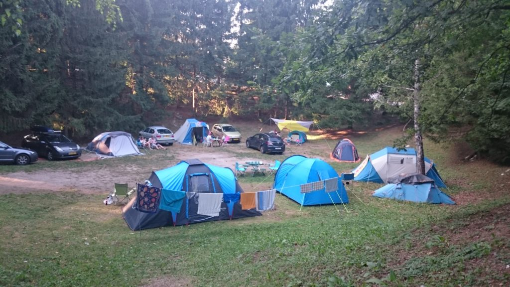 On a field in 'ditch'are tents pitched in a circle with cars in between. Behind trees. Campsites in Croatia.