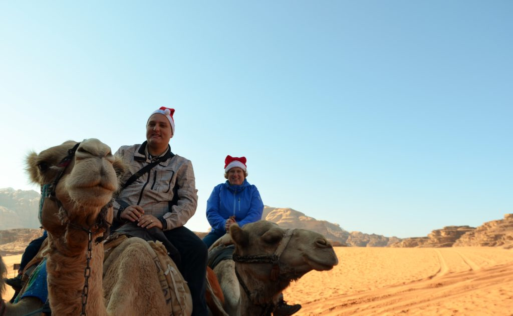 A picture to show what we did on Christmas morning. Cosette and Paul on camels with a Christmas hat on their head. The desert behind them.