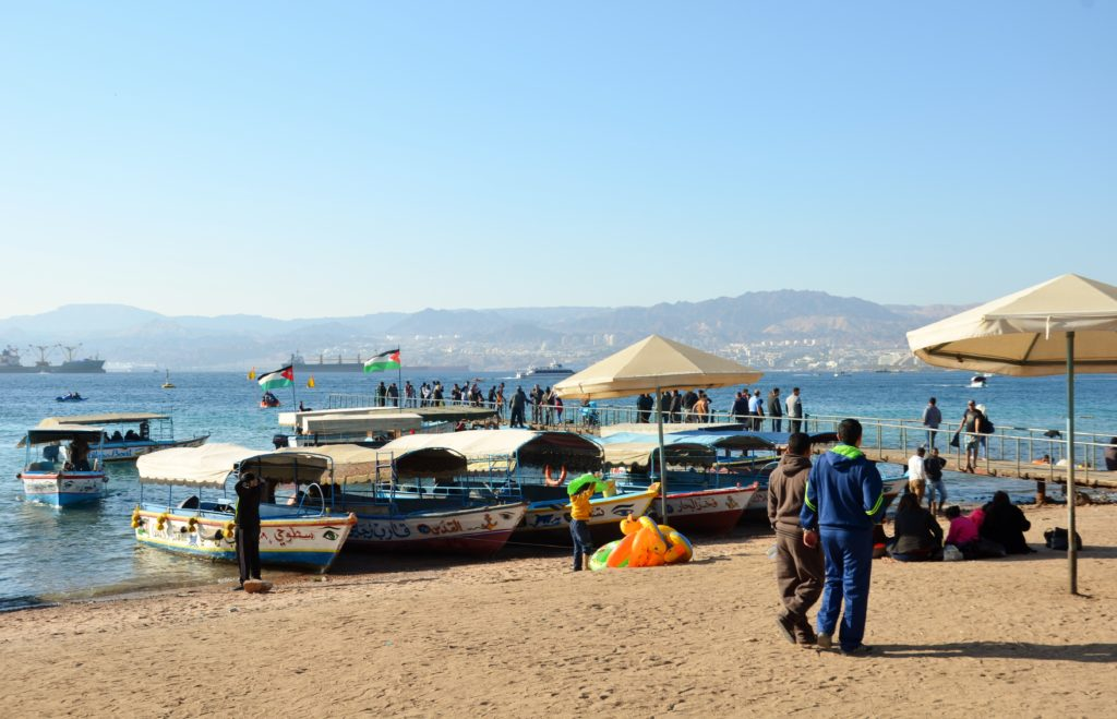 To show that we good go the beach. Beach, glass bottom boats on the Red Sea. People walking on the beach. Mountains in the back.