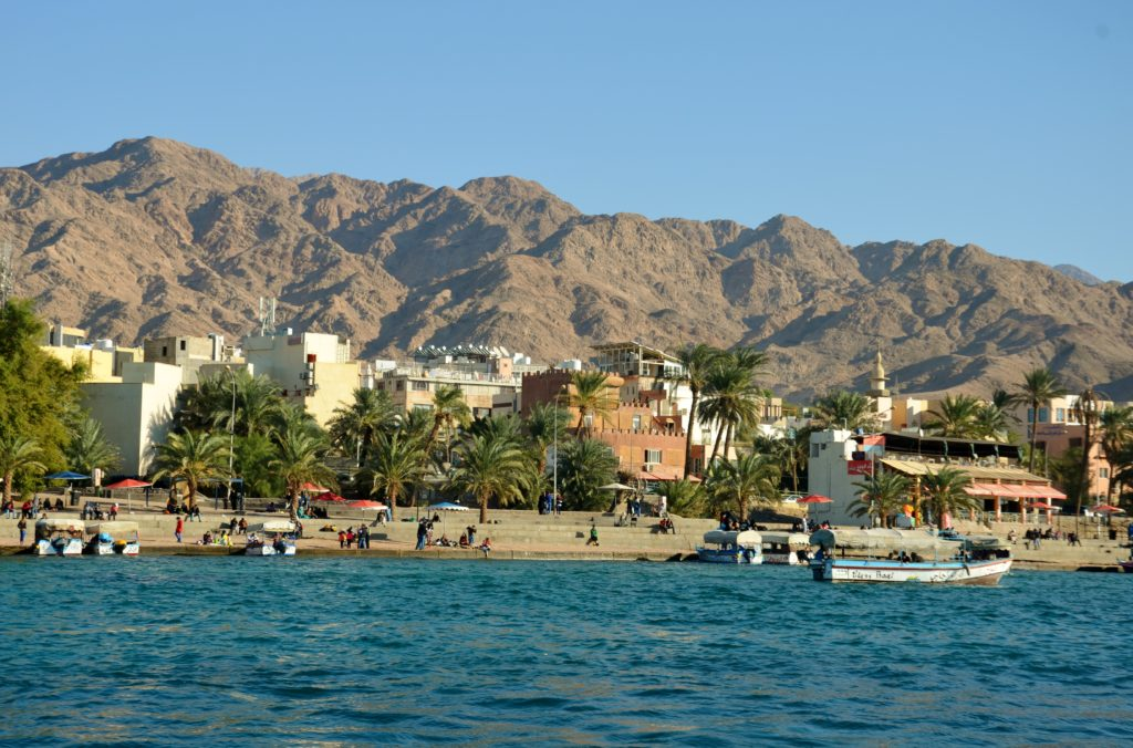 To show a picture of Aqaba. Picture taken from the sea. The water looks blue, behind is the beach with palm trees. Houses behind and behind the houses mountains and a clear blue sky. Tour through Jordan.