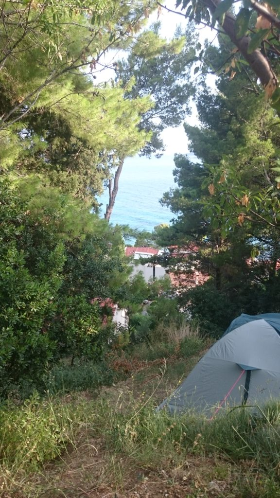 In the right corner our blue tent. For the rest trees, with a see through on the ocean, way down. Campsites in Croatia.
