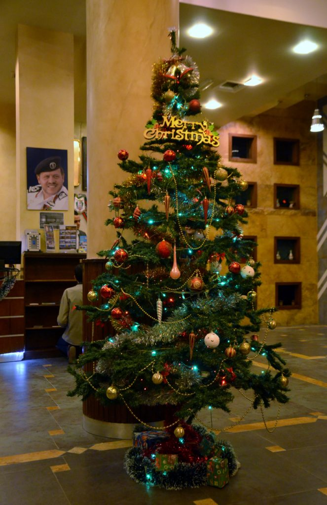 To show a picture that there are Christmas trees in Jordan. A decorated fake Christmas tree in a hotel lobby. A desk behind it and a picture of the king.