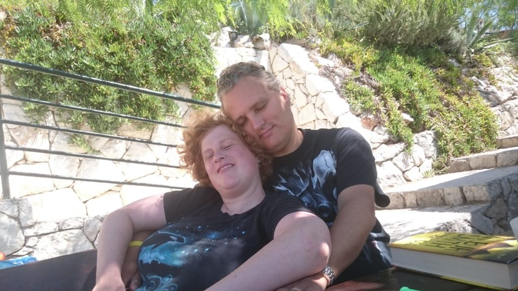 Cosette is sitting against Paul. Paul has his arms around Cosette. Both are wearing black tshirts. Behind them a fence and green trees and bushes. Long term traveling.