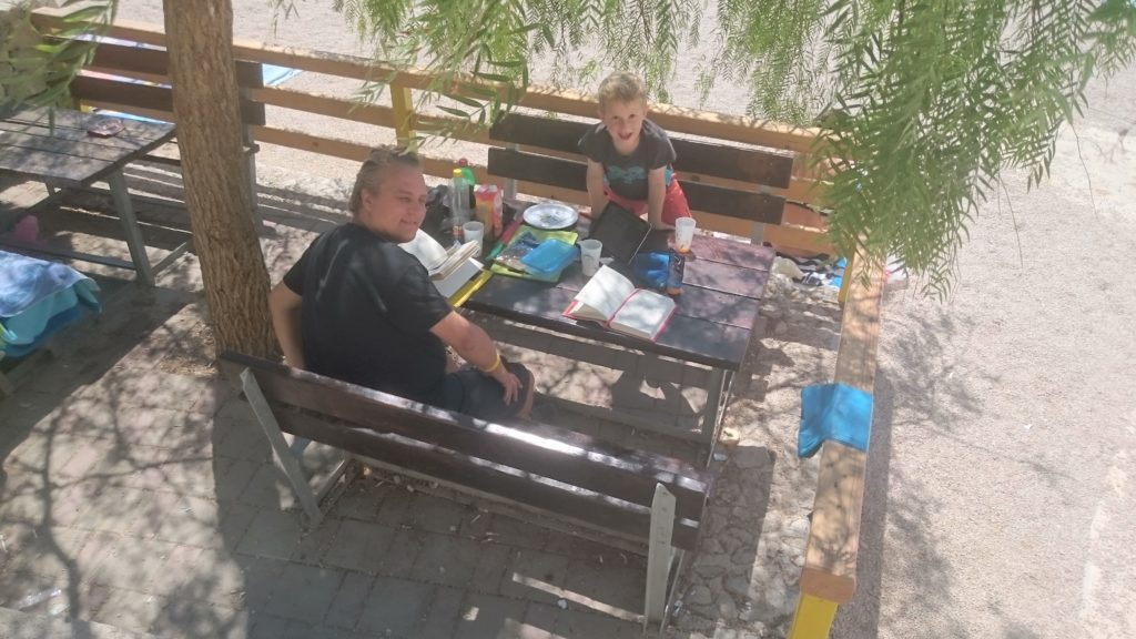 Looking down on a bench where Paul and Yuri are sitting on. A tree giving shade to them. A table in between with all sorts of stuff on it. Long term traveling.