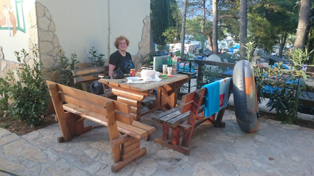 A wooden table surrounded by 3 wooden benches. On the right bench there are hanging 2 towels to dry. A tube is tanding against it. On the table is dinner set out. I'm sitting on the bench at the back. A railing at the back and a wall behind me.