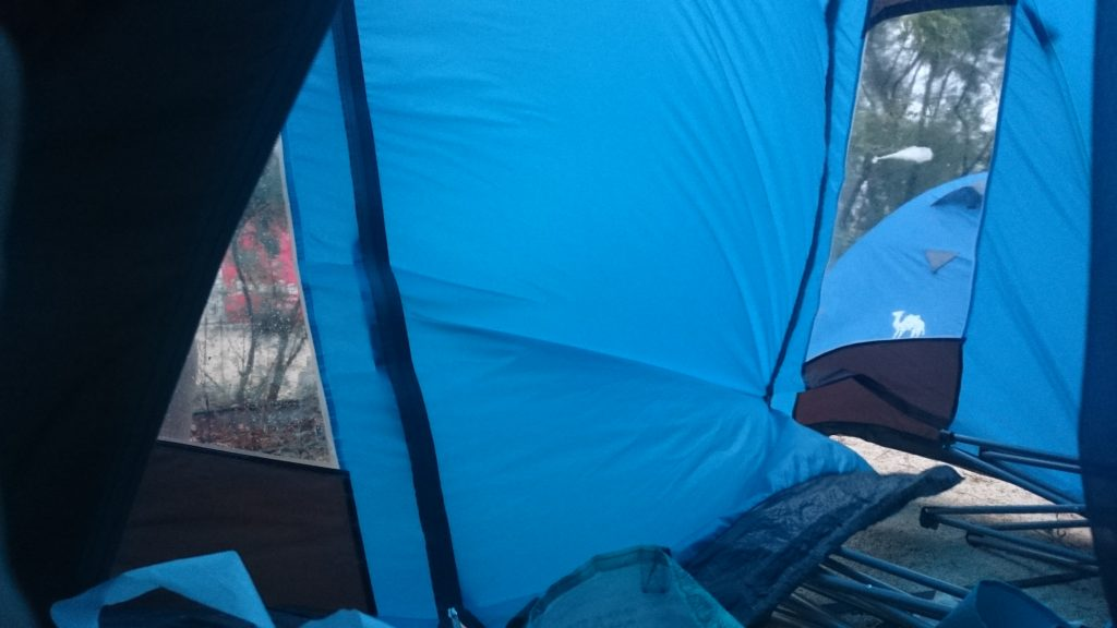 The entrance to a tent, a blue one is blowing up in the wind.