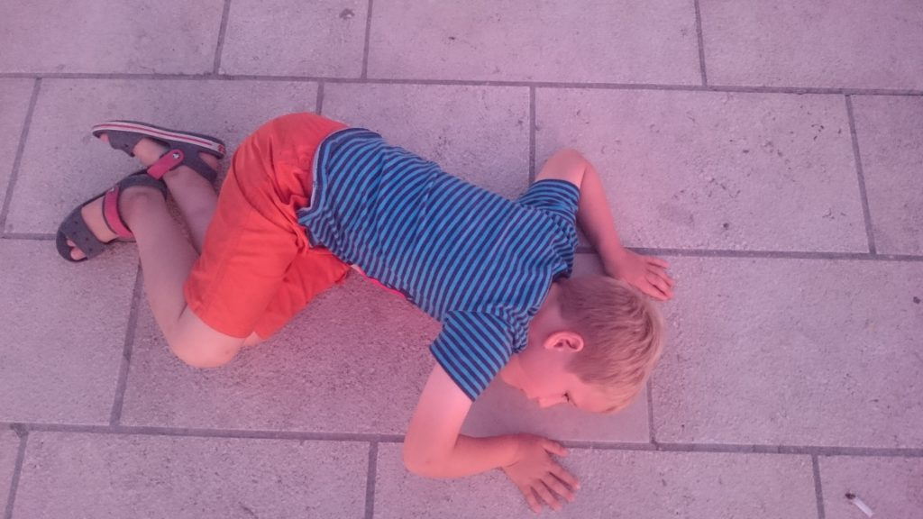 Yuri has a blue shirt on and a orange short. He's laying on the ground listening to the sea organ in Zagreb, Croatia.