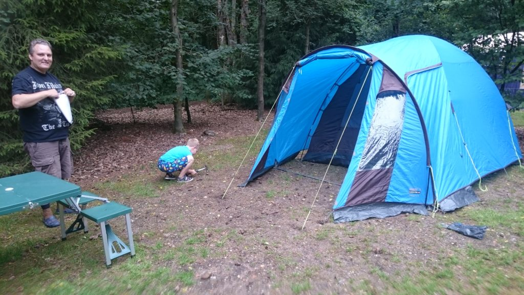 To show the size of the spots to camp on. A grass field surrounded by pine trees and other trees. The grass is away on some places and there's just sand. Our blue tent is on it and our pic nic table and Yuri is playing in the middle. Campsites in The Netherlands.