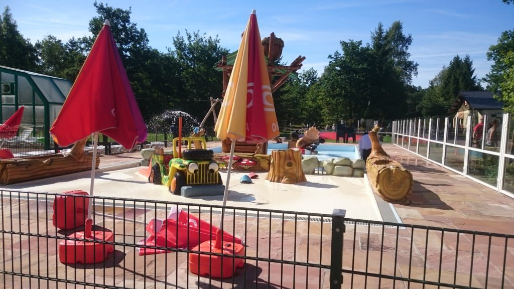 To show the kiddie pool, large and surrounded by a fence.