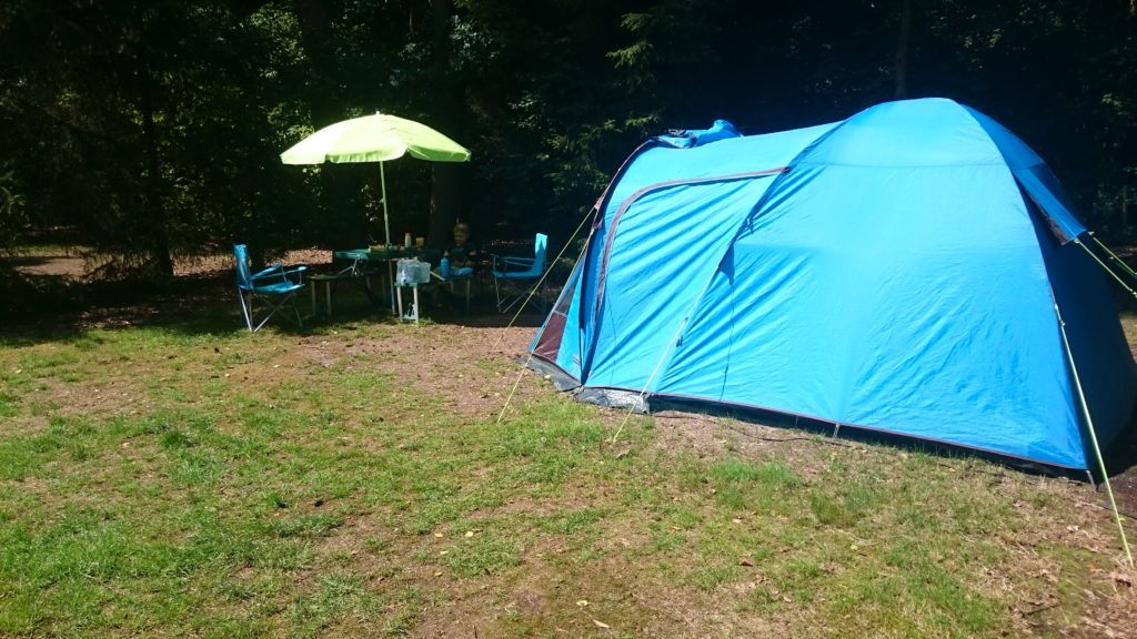 To show our spot from a different angle. Our tent at our spot with the sun shining. Blue tent, pic nic table, stuff around and a parasol out.