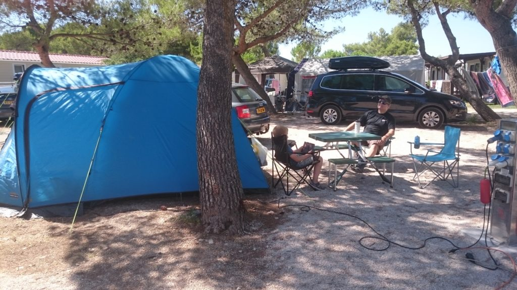 In the forefront a tree, behind that our blue tent. Next to it Yuri and Paul are sitting on chairs with  picnic table in between. Behind them cars and trees. Campsites in Croatia.