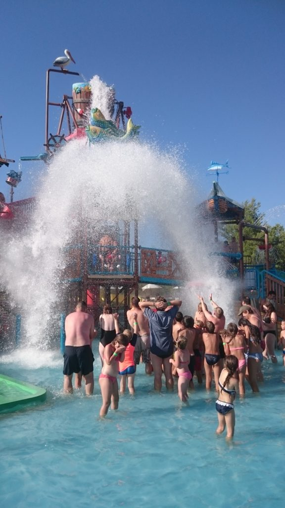 People being splashed by the waterbucket that drops.