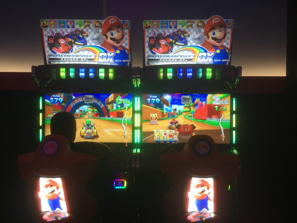 Two machines with Mario Kart on them. You see the screens and aplate with a picture of the game above. In front are two chairs with stirring wheels and a picture of Mario on the back. Paul is sitting on the left, Yuri in the right chair. Utrecht with kids.