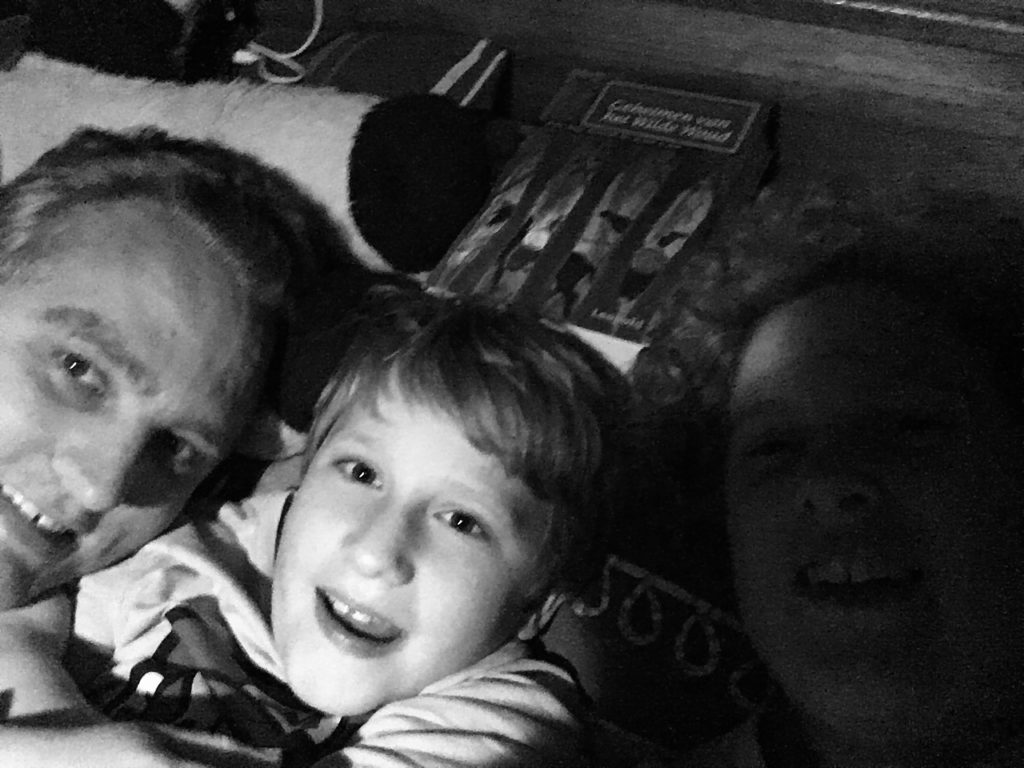 A black and white picture of the 3 of us. Paul on the lift, Yuri in the middle, Cosette on the right. A book behind Yuri's head. In the bed in the camper van. Van life.