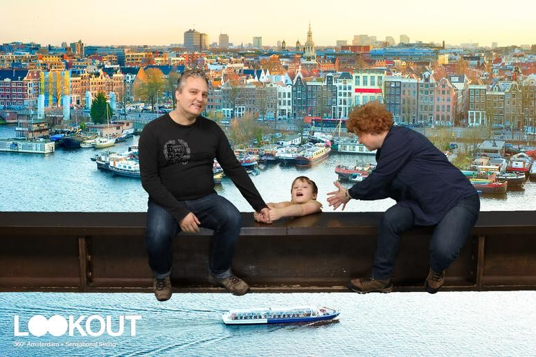 A picture to show something from October travels. It's a staged picture taken on a beam. In front of a green screen. The green screen shows a still of Amsterdam. Yuri's fallen of the beam, Cosetee tries to grap him. Yuri is holding on tight on Paul's hand. Paul looks into the camera.