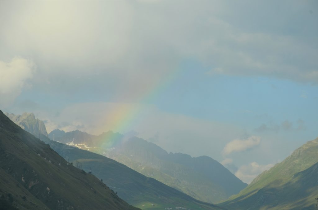 To show A rainbow coming out of the mountains