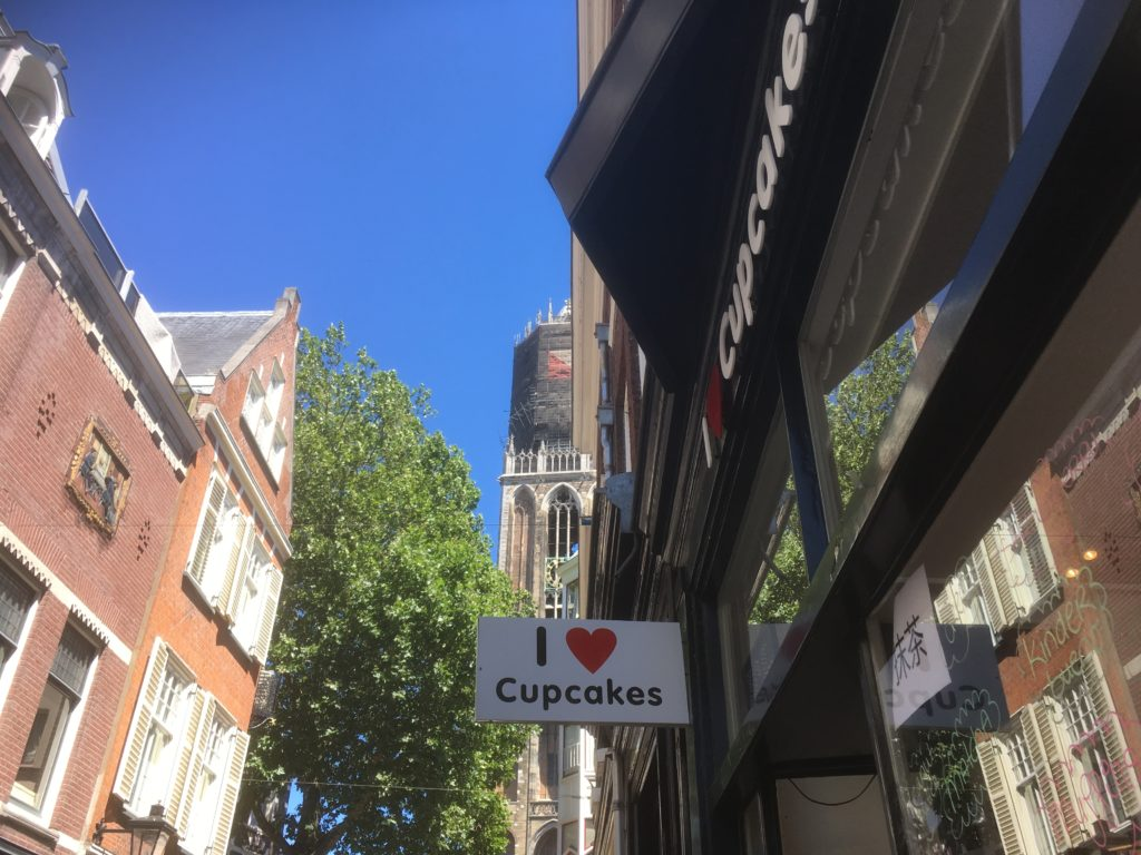 To show the sign of the shop with the Dom Tower and clear blue sky i the back. Eat in Utrecht