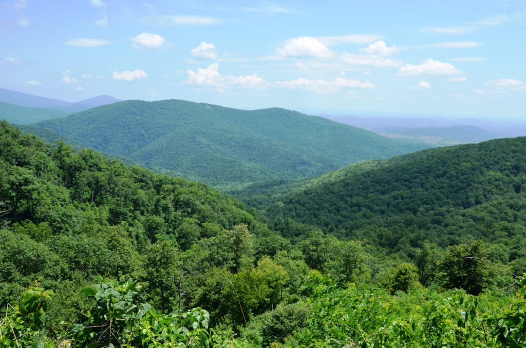 One of our first views on the BLue Ridge Mountains. A few clouds in the sky, green mountains below with some shadows.