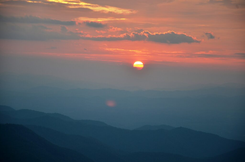 Sunset on the Blue Ridge Parkway. The sun goes down with a red and blue sky above the mountains.
