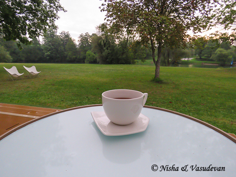 A table in the front with a cup of coffee on it. Behind a grass field with trees.