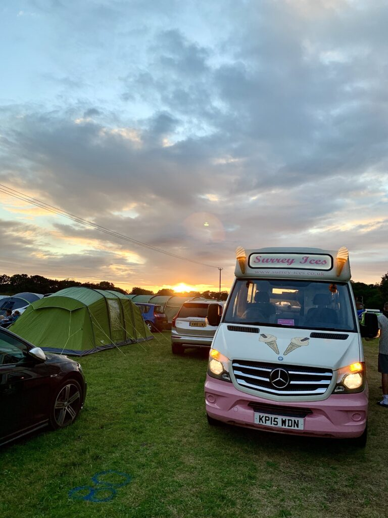 On the left an ice cream van on a grass field with for the rest tents and cars on it. Overcast sky above.