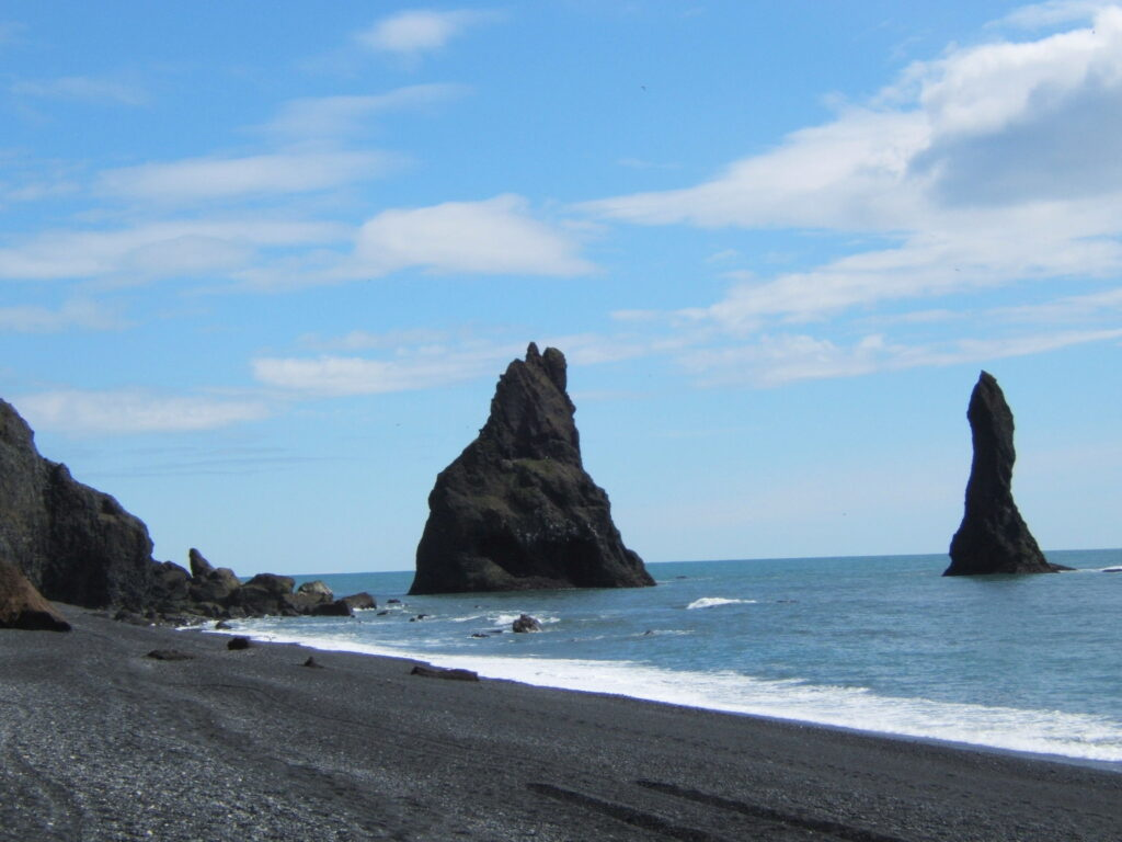 Black sand beach, with the sea on the right. Basalt rocks coming out of the ocean. A blue sky with a few white clouds.