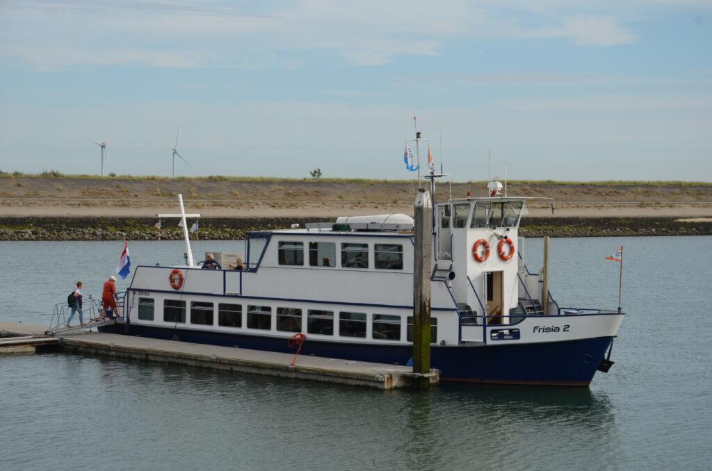Rondvaartboot voor Oosterschelde Nationaal Park, boot die aan de kade ligt, twee mensen gaan net aan boord.