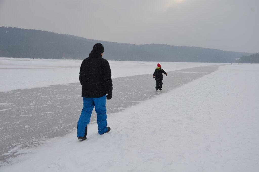 Paul walking on the lake, next to the track. Yuri ice skating in front of him on the track.