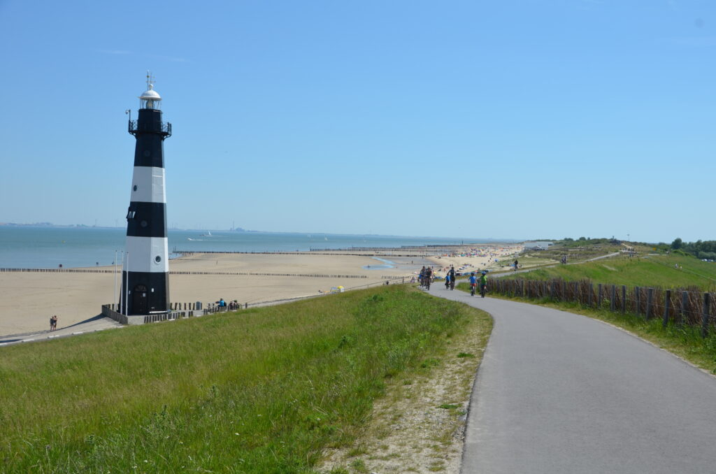 Path on the dunes. On the left an light house and after that the beach and sea. People biking on the path.