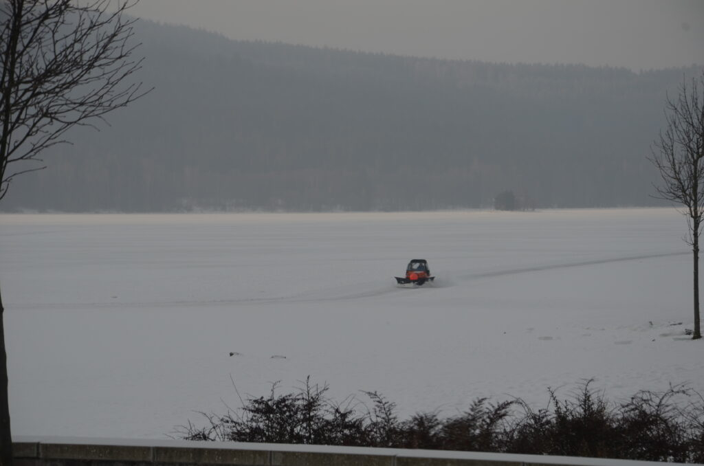 Keeping the track free of snow. A zamboni is riding on the track on the lake. Seen from the shore.