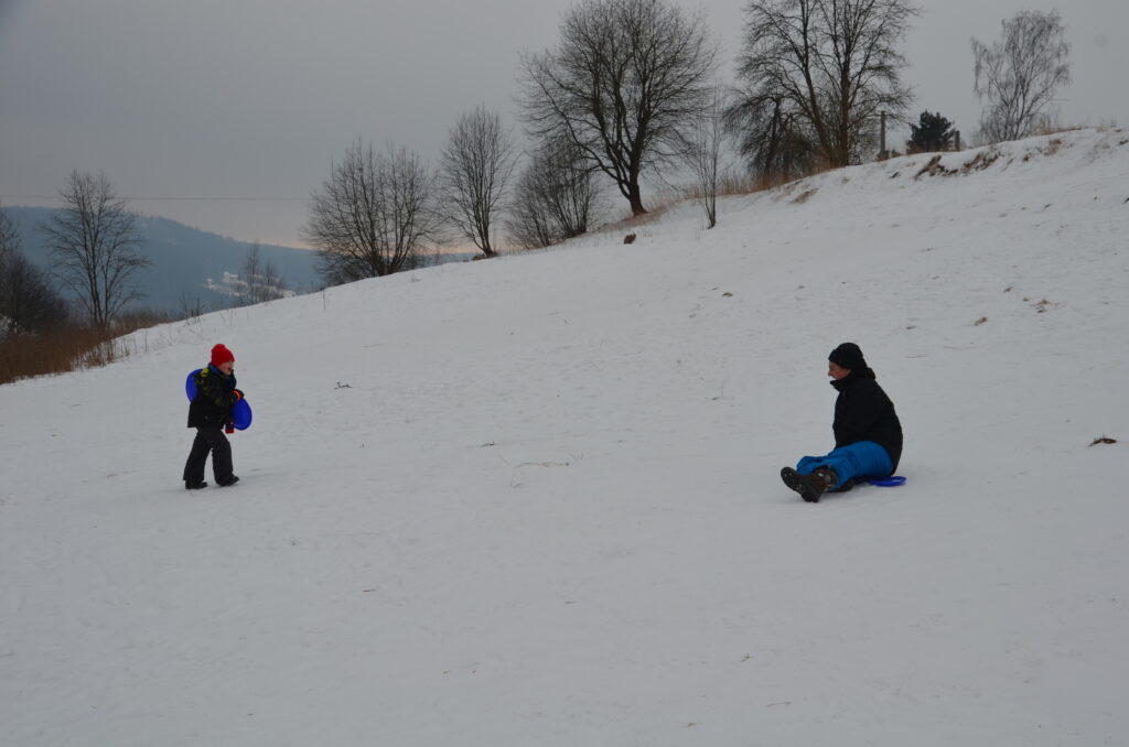 Paul and Yuri sledding on the mountain. A mountaimn covered in snow. Paul has just stopped and Yuri  walking up with his sled again
