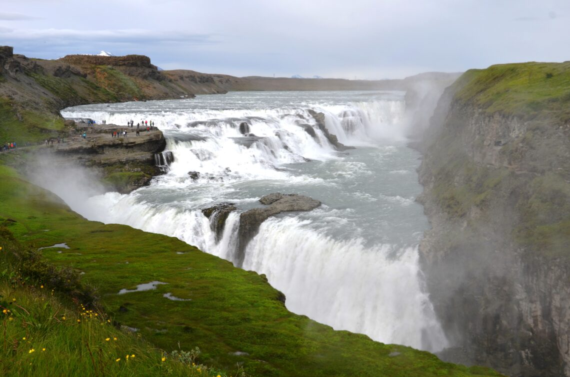 An overview of Gullfoss, the 2 traps, green grass field in the front.