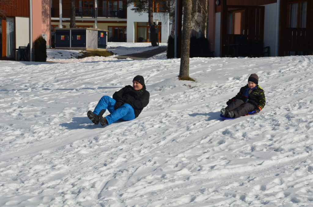 Paul and Yuri sledding on the park. Some cabins behind them. Lots of snow.