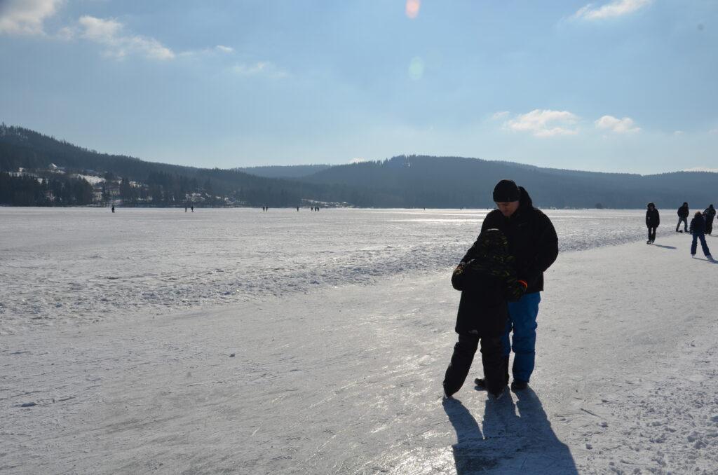 Paul learning Yuri how to ice skate. Paul is holding Yuri's hands, walking backwards, while Yuri skates.