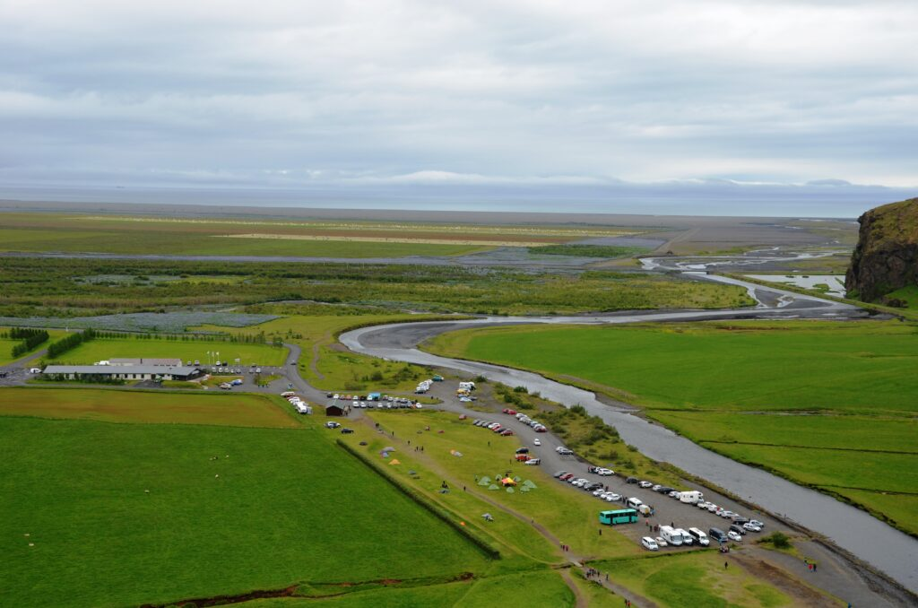 The view from on top of Skogafoss. The green fields, river, road, cars on the parking lot and the sea in the distance. An overcast sky.