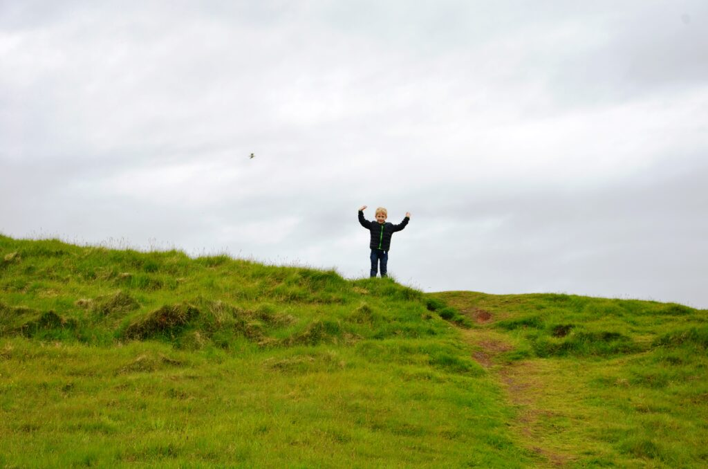 Yuri waving from on top, standing on a hilly grass field