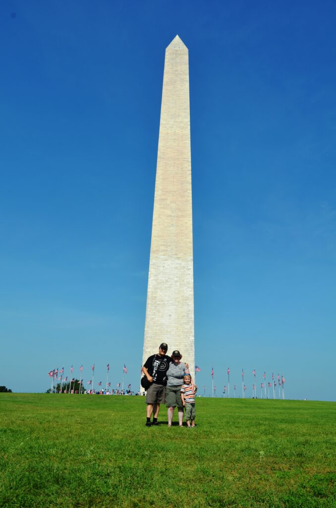 Us in front of the Washington Monument. Us 3 standing on a large grass field, we're small in the picture. Blue sky behind us. The pinnacle/obelisk directly behind us.