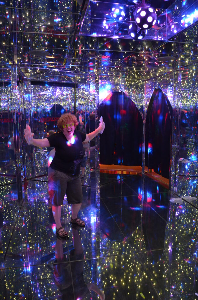 Inside the Mirror Maze. Cosette standing on the left side of the photo. With 3D glasses on. Surrounded by mirrors. Posing for the camera in a joly way.