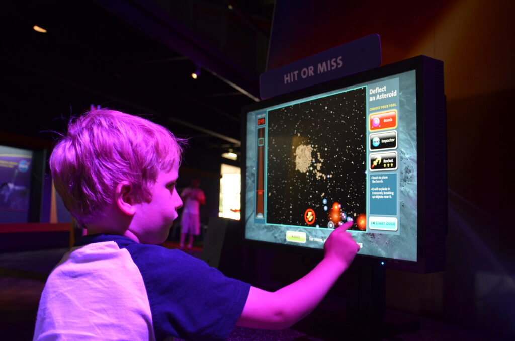 Yuri playing at the Kennedy Space Center. Yuri is on the left side of the picture. Touching a screen in front of him with his finger and trying to avoid an stroid.