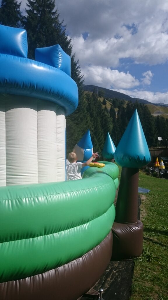 Bouncy Castle at Camping Disentis, a family friendly campground in Europe. Yuri is standing in the bouncing castle. Behind you see the mountains grass and a bit of the terrace from the restaurant
