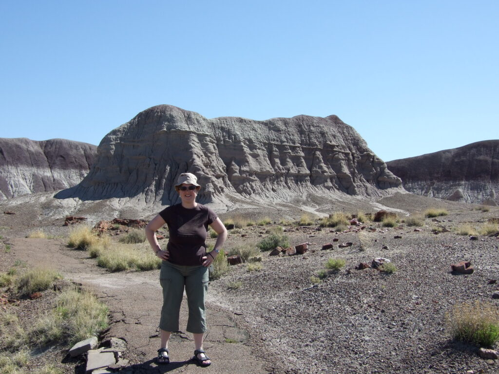 Cosette on the trail, behind her gray badlands. The rest is grasses and sand around her. she stand on a paved road.