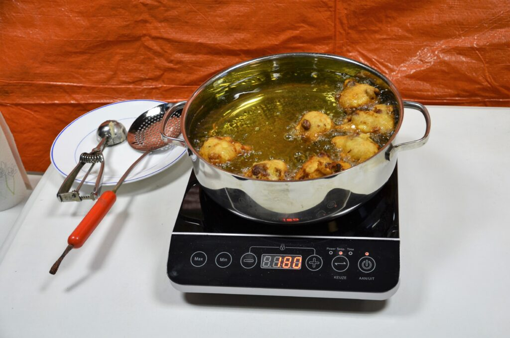 Baking oliebollen, a boiling pan with oil with oliebollen in them.