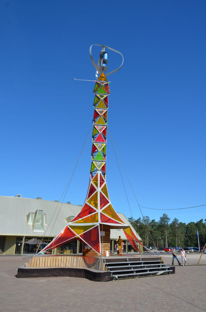 Solar panels in the form of art. A tower in yellow, red and green on a square.