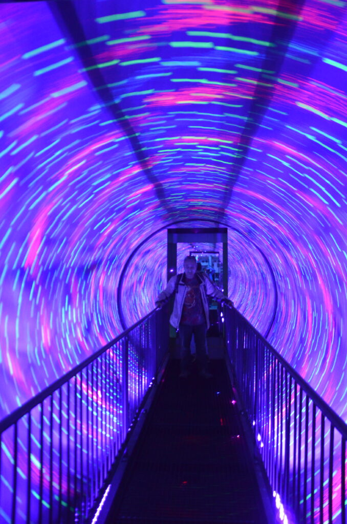 The tunnel at Ripley's Believe It or NOt. Blue and pink stripes. Paul standing in the middle.