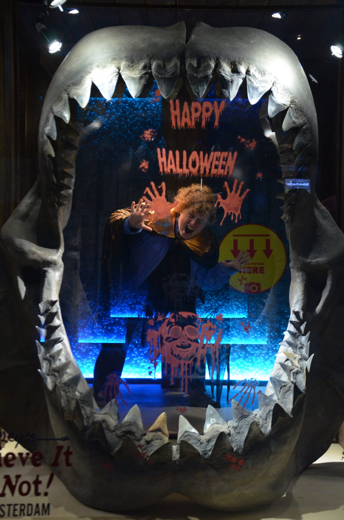 Happy Halloween! on a glass plate , where Cosette is standing behind, in between jaws teeth.