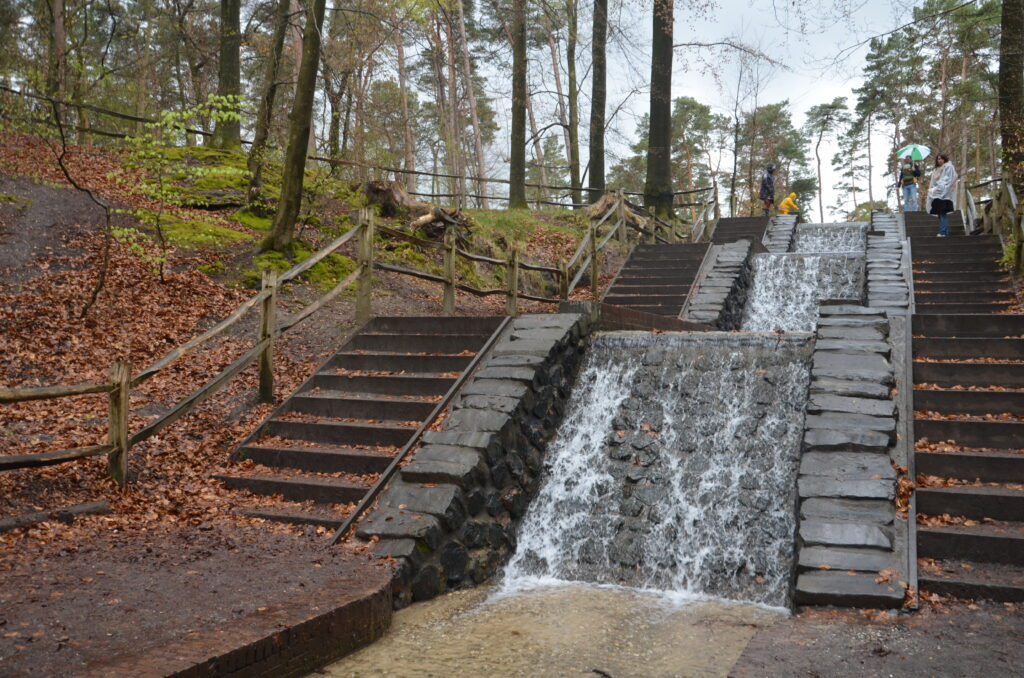 Loenense waterfall on a rainy day, one of 30 beautiful waterfalls in Europe, dropping down on 3 toers, man made, stairs going down next to it on both sides. Forest next to the stairs on both sides