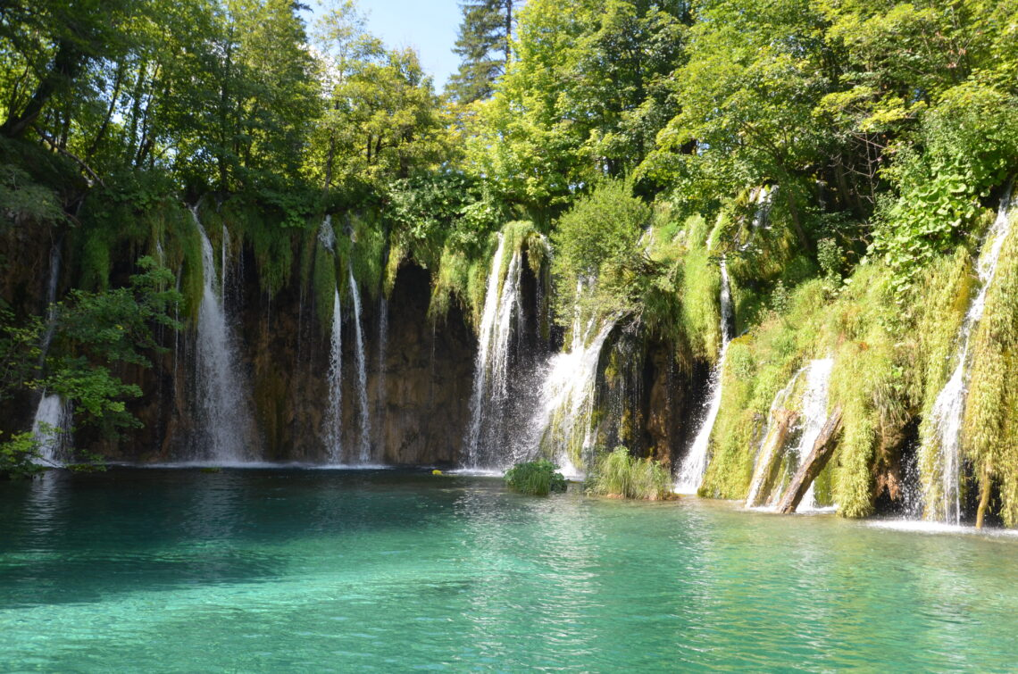 Plitvice Falls, small streams dropping down in a clear greenish lake